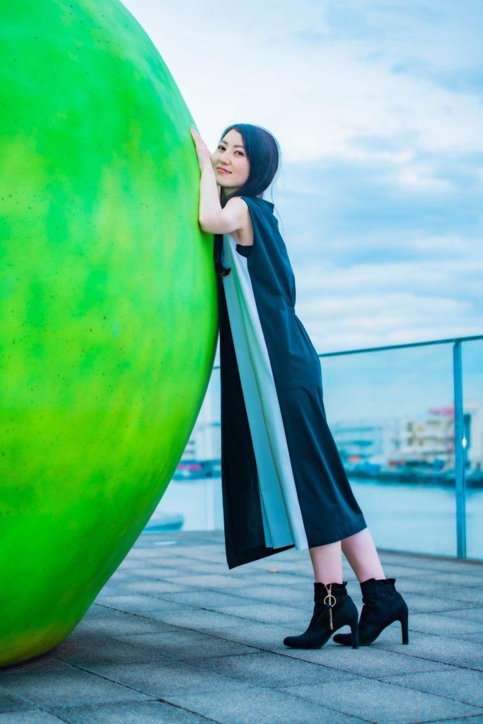 アクセントになるグリーンのリンゴに身を寄せるキュートな女性の写真